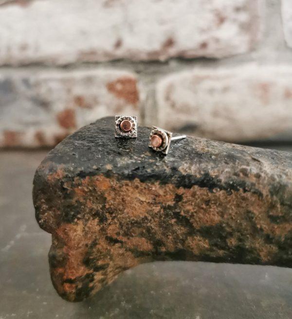 stud earrings sitting on a cobblers last