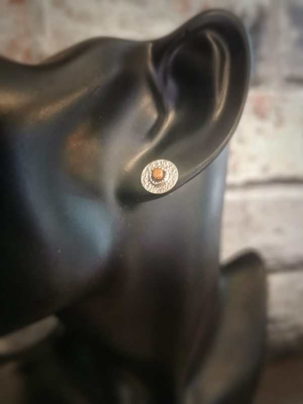 a plastic display head showing a sterling silver and copper circle stud earring