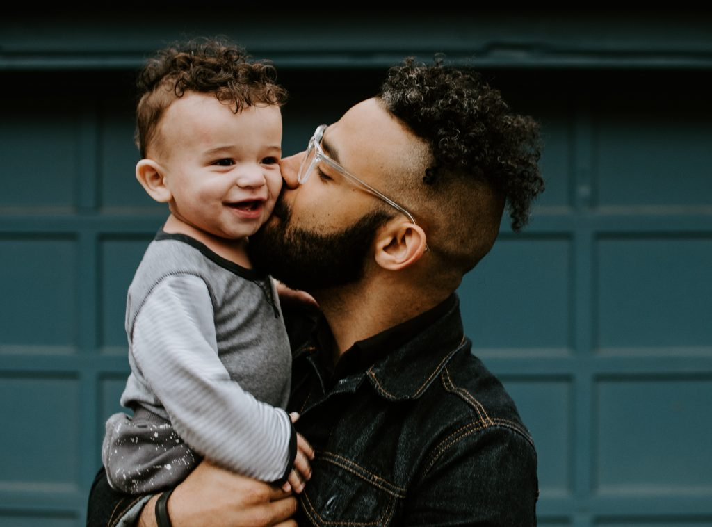 Father kissing son whilst holding him in his arms on Father's Day- fathers day blog